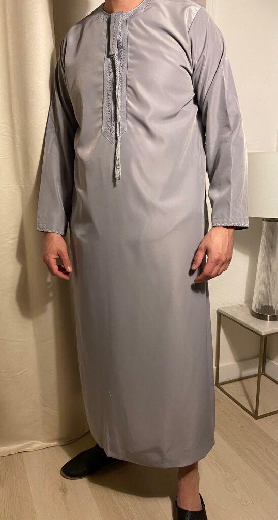 Qamis Emirati Gris Avec Cordon – هواهينغ ou Abaya homme, se décline en plusieurs modèles. Ce modèle trouve son origine aux Emirats Arabes